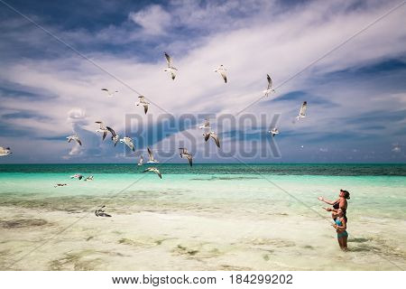 Cayo Coco island, Cuba,  Sep.10, 2015, Local  woman and little girl enjoying their leisure time on the beach, feeding flying seagulls, on sunny great day