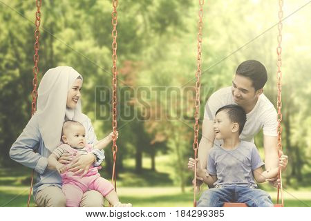 Portrait of two cheerful muslim family and their children having fun together on the swing at the park