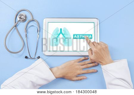 Top view of a doctor's hand pressing a tablet screen with lungs symbol and asthma word