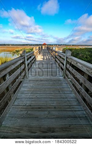 A wooden bridge leading to swamp land