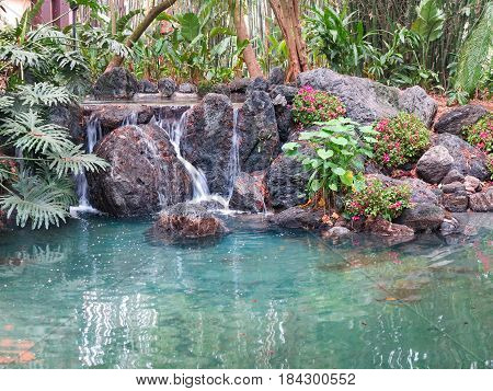 A small waterfall over rocks into pond
