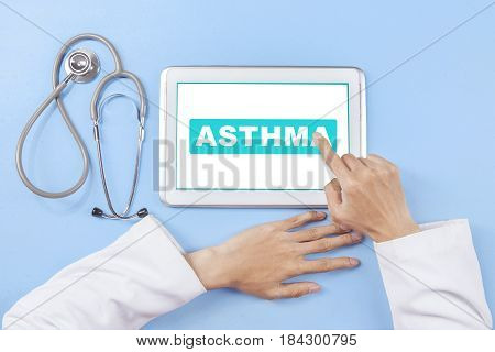Hands of male doctor touching asthma word on the screen digital tablet with a stethoscope on the table