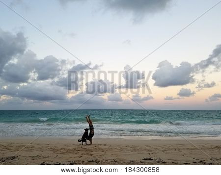Man Handstanding on beach at Dusk with Dog spotting the pose as wave crash on the Waimanalo Beach on Oahu Hawaii.