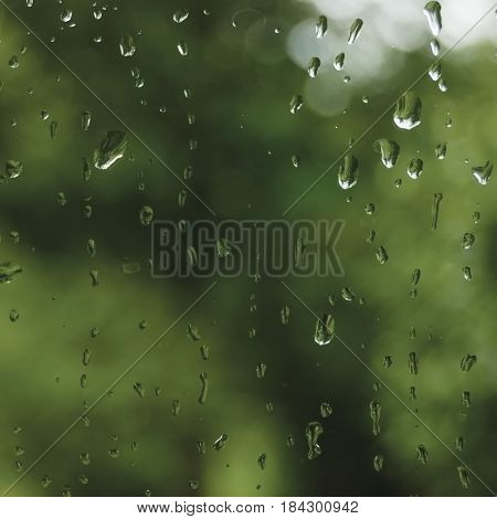 Rainy summer day raindrops on wet window glass bright abstract rain water background pattern detail macro closeup detailed green blue dark vivid gray waterdrops gentle bokeh pluvial rainfall season concept