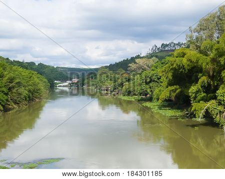 Panoramica of tranquil river current and banks with forests in day of clouds