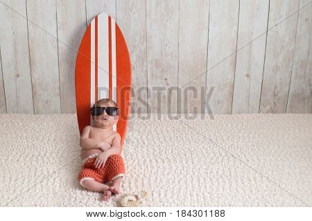 Nine day old newborn baby boy leaning against a tiny orange and white surfboard. He is wearing orange crocheted board shorts.