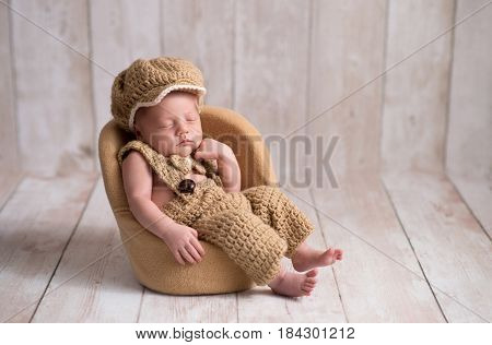 Nine day old newborn baby boy wearing a crocheted little man suit with newsboy cap and bowtie. He is sleeping in a tiny chair with a fist under his chin.