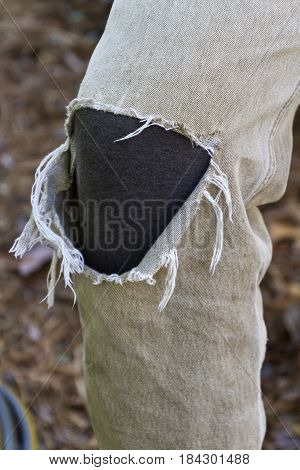 Close up of a frayed knee section in the fabric of a pair of khaki pants with a dark underlayer of fabric showing through worn by a person working outdoors