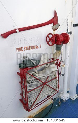 Fire station mounted on a ferry boat wall consisting of an axe and a long water hose to put out fires aboard