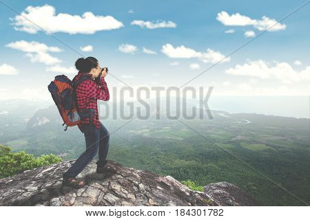 Rear view of male traveler standing on the mountain while taking photo and carrying backpack