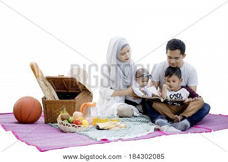 Picture of Muslim family enjoying a picnic while reading a book and sitting in the studio