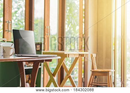 Laptop blank screen on wooden desk and chair in room interior with morning light