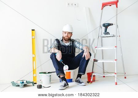 Upset young man resting on bucket while making repair in house