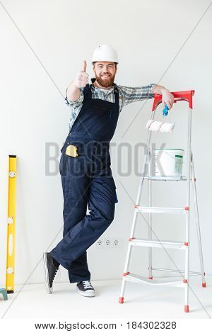 Young man leaning on ladder and showing thumb up while making repair isolated