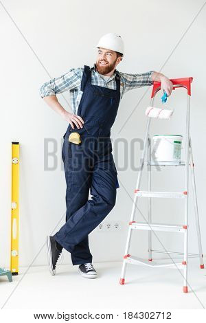 Young man leaning on ladder looking away while making repair isolated