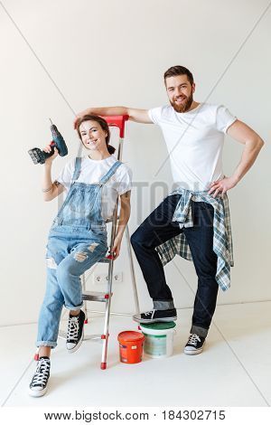 Pretty couple, man and woman, with repair equipment standing near ladder isolated