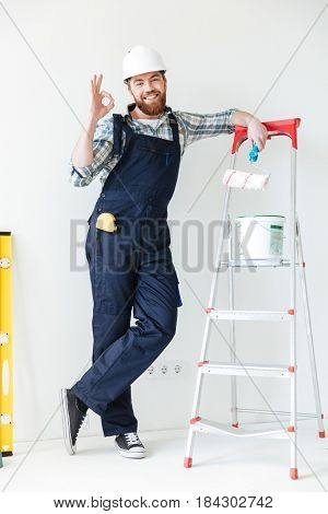 Young man leaning on ladder and showing ok gesture while making repair isolated