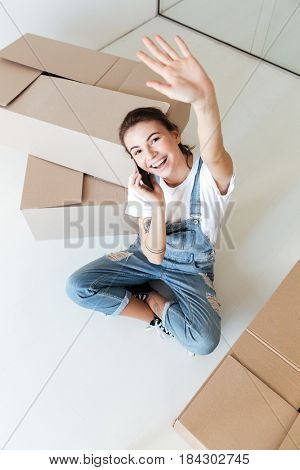 Young smiling talking on phone and waving hand near boxes