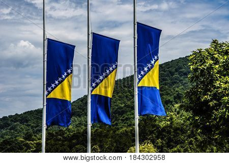 Three Bosnian flags on metal posts with green trees and blue sky as background. Flag of Bosnia and Herzegovina, National flag of Bosnia, New Bosnian flags