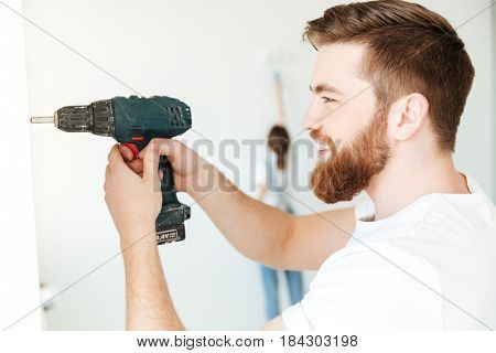 Portrait of cheerful bearded man using drill to make repair isolated