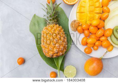Pineapple mango granadilla kumquat fizalis melon orange on a gray background. Exotic fruits