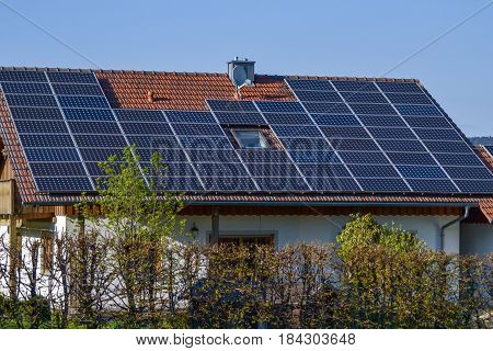 Solar panel on a red roof reflecting the sun and the cloudless blue sky