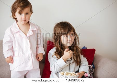 Cute children eating popcorn from dish while sitting on sofa