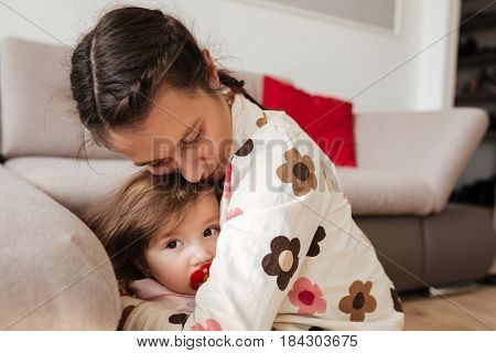 Close up of young mother hugging her child with love and care in living room