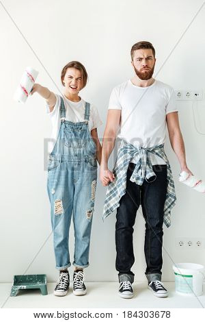 Angry builders man and young woman worry about something isolated