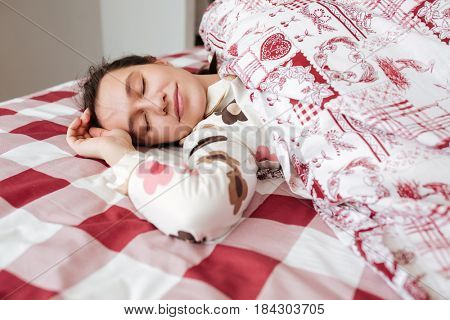 Young woman sleeping peacefully in bed with blanket