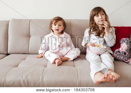 Pensive children in pajamas eating popcorn on sofa