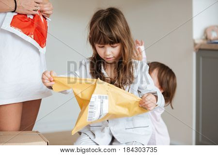 Little girl with ling brown hair tearing up a package with mail at home