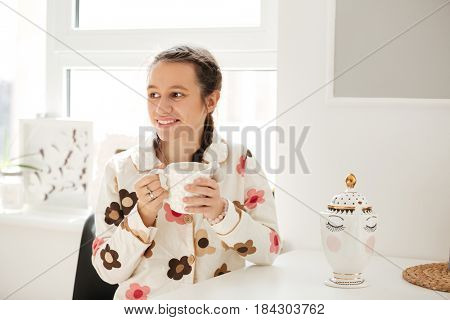 Cheerful young woman wearing pajamas drinking coffee and sitting in kitchen
