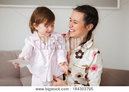 Cheerful mother hiding her daughter while they sitting on sofa