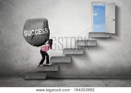 Female entrepreneur carries a boulder with Success word on her back while walking on the stairs toward a door