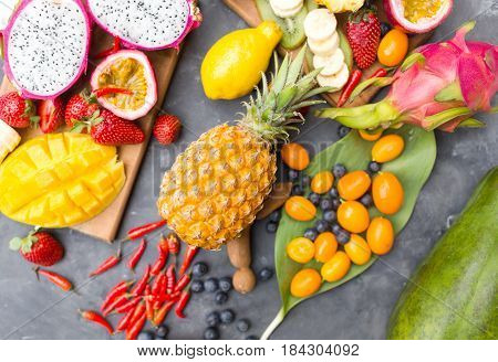 Exotic fruits. Summer photo concept. Mango. Papaya. A pineapple. Avocado. Kiwi. Pitahaya. Kumhvat. Copyspase. Fresh fruits. Exotic fruits on a gray background. Blueberry. Strawberry. Physalis. Tamarind. Lemon.