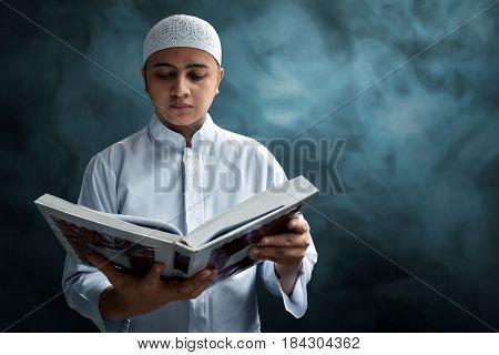 Muslim man reading koran with smoke background