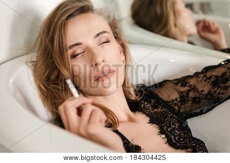 Portrait of Young cute woman with closed eyes enjoying smoking