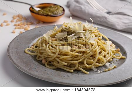Spaghetti with pesto sauce, Parmesan cheese, and pine nuts