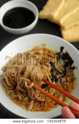 Traditional Japanese soba soup with carrot, onion, nori, tofu, and soy sauce