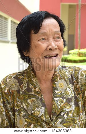 An elderly asian woman laughing outdoor happily