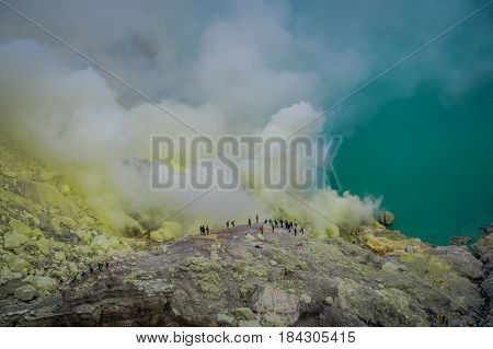 KAWEH IJEN, INDONESIA: Tourist hikers with backpacks and facial masks seen overlooking sulfur mine and volcanic crater.
