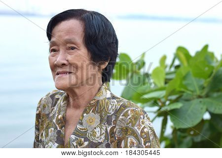 An elderly asian woman smiling happily outdoor
