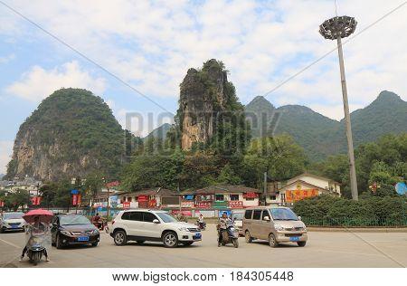 YANGSHOU CHINA - NOVEMBER 18, 2016: Unidentified people drive in Yangshou town centre.