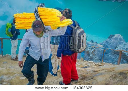KAWEH IJEN, INDONESIA - 3 MARCH, 2017: Local miners carrying heavy loads of yellow sulfur rocks up mountain side, tourist hiking attraction located inside volcanic crater, spectacular nature.