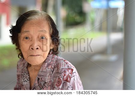 An elderly asian woman doing a funny look