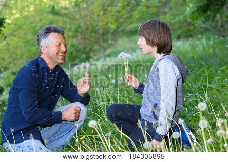 Man with his son blowing dandelions over blurred green grass, summer nature outdoor