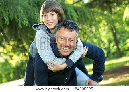 Portrait of father with his son having fun in summer park. Piggyback. Family fun. Happy boy playing with dad summer nature outdoor. Family leisure