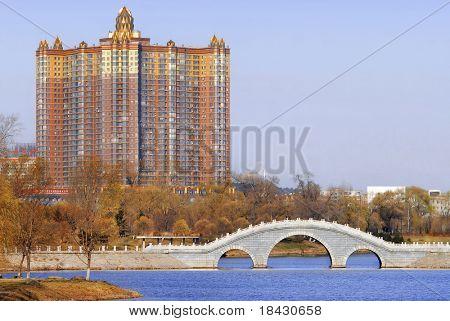 Residential skyscraper and public park in Jilin. North China city in autumn season. Oriental bridge.