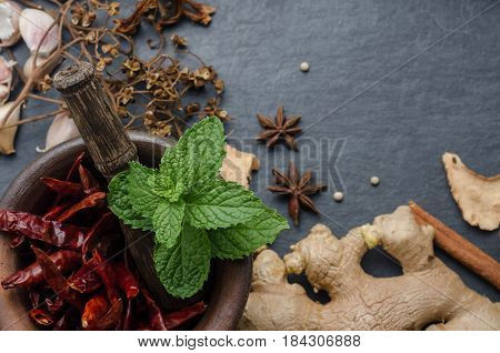 Dried chili in small mortar with various ingredients herbs on black stone background. Top view with copy space